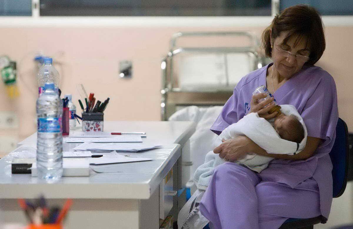 Personal de Enfermería de la Sala de Neonatología alimenta con biberón a un recién nacido